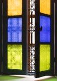 Fönster med kulört exponeringsglas och arabiskt galler i Marrakesh Arkivbilder