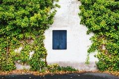 Fönster med stängda träslutare i lantligt hus Arkivbilder