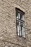 Fönster med stänger på tegelstenväggen Arkivfoto