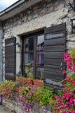 Fönster med träslutare blommar fönsterbräda Ett gammalt europeiskt hus royaltyfri fotografi
