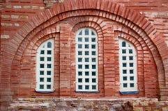 Fönster och åldrig tegelstenbyggnad arkivbild