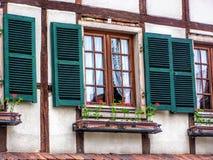 Fönster och husvägg med röda blommor i en fönsterask i Strasbourg Alsace Frankrike royaltyfria bilder