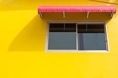 Fönster på den gula väggen med den röda splashboarden arkivfoto