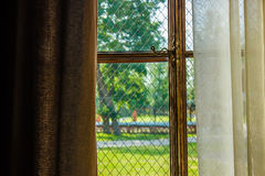 Fönster som täckas med gardiner med den förgyllda fönsterramen, lyx VI arkivfoto