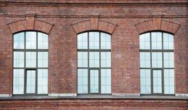 Fönster tre på en röd bric vägg Arkivbild