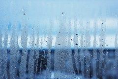 Fönsterexponeringsglas i condensaten i de kalla strömmarna av vattnet tappar bakgrund arkivbild