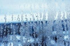 Fönsterexponeringsglas i condensaten i de kalla strömmarna av vattnet tappar bakgrund royaltyfria foton