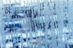 Fönsterexponeringsglas i condensaten i de kalla strömmarna av vattnet tappar bakgrund royaltyfri fotografi