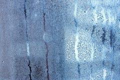 Fönsterexponeringsglas i condensaten i de kalla strömmarna av vattnet tappar bakgrund royaltyfri bild