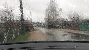 Fönsterexponeringsglas, regnig dag, regndroppar på vindrutabilen stock video