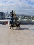 Fönsterlokalvårdanställd med arbetshjälpmedel och stadsbakgrund Royaltyfria Foton
