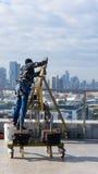 Fönsterlokalvårdanställd med arbetshjälpmedel och stadsbakgrund Royaltyfri Foto