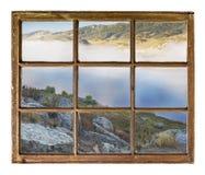 Fönstersikt - dal och sjö i dimma Royaltyfri Bild