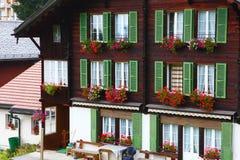 Fönstret blommar på byggnaden i Wengen, Schweiz Arkivfoto