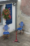 Fönstret med blått stänger med fönsterluckor i couryard med stolar arkivfoto