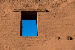 Fönstret som visar blå himmel i en Adobevägg på, fördärvar i Pecos som nationellt historiskt parkerar, nytt - Mexiko royaltyfri foto