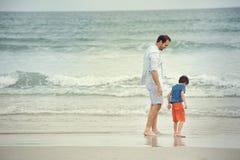 Förälder och barn på stranden Arkivfoto