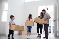Förälder och ungar med kartongen house att flytta sig som är nytt till royaltyfria bilder