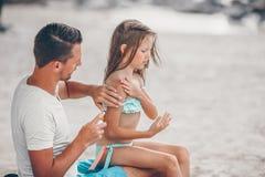 Förälder som applicerar solkräm till ungenäsan Stående av lttleflickan i suncream royaltyfria foton