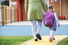 Förälder som Pre tar barnet till skolan arkivfoto