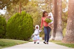 Förälder som tar barn trick eller behandlar på allhelgonaaftonen arkivbild