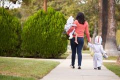 Förälder som tar barn trick eller behandlar på allhelgonaaftonen royaltyfri fotografi