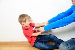 Förälder som ut tar handlagblocket från barn arkivfoton