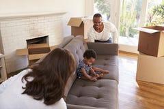 FörälderCarry Son On Sofa Into nytt hem på rörande dag arkivfoto