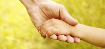 Föräldern rymmer handen av ett småbarn Arkivbild