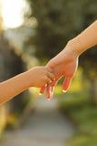 Föräldern rymmer handen av ett småbarn Arkivfoton