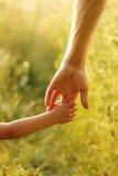 Föräldern rymmer handen av ett småbarn Arkivbilder
