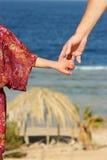Föräldern rymmer handen för barn` s på havet Arkivfoton