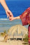 Föräldern rymmer handen för barn` s på havet Royaltyfri Fotografi