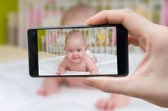 Föräldern tar fotoet av en behandla som ett barn med smartphonen Arkivfoto