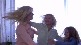 Föräldra- förälskelse, mamma hoppar på säng med hennes döttrar och kramar därefter tillsammans arkivfilmer