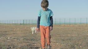 föräldralös Övergett ensamt barn på område av flyktinglägret pojke i smutsig trådsliten kläder som rymmer littl för flott kanin f lager videofilmer