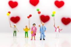 Föräldrar älskar sig lyckligt, med barn som spelar ballonger, är bakom, använt som ett bröllopsdagbegrepp Arkivbilder