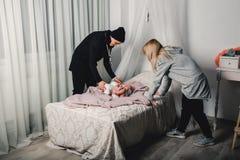 föräldrar ändrar det litet behandla som ett barn på sängen royaltyfri fotografi