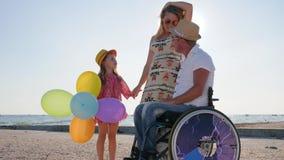 Föräldrar berättar av moderskap, rörelsehindrad person i rullstol med familjen, lyssnar lilla flickan modern och fadern på hjulet lager videofilmer