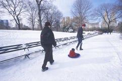Föräldrar drar barnet i släde i Central Park, Manhattan, New York City, NY efter vintersnö Arkivfoto