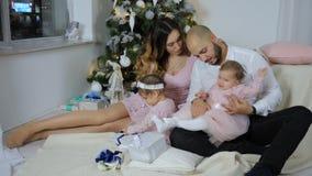 Föräldrar för nytt år har gyckel med döttrar på bakgrund av det upplysta julträdet på vardagsrum stock video