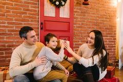 Föräldrar ger barnet en gåva för jul arkivfoton