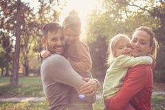 Föräldrar ger döttrar för en kram Lycklig le familj royaltyfria foton