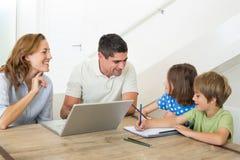 Föräldrar med bärbara datorn som hjälper att färga för barn royaltyfri bild