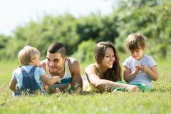 Föräldrar med barn som lägger i gräset Arkivfoto