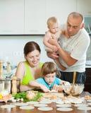 Föräldrar med barnklimpar fiskar matlagning i ett hem- kök arkivbilder