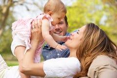 Föräldrar med behandla som ett barn flickan som sitter i fält Royaltyfri Fotografi