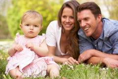 Föräldrar med behandla som ett barn flickan som sitter i fält arkivbilder