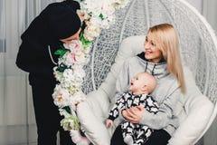 Föräldrar med behandla som ett barn på gungan i rummet ler royaltyfri fotografi