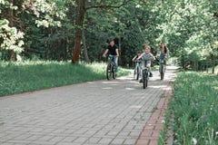 Föräldrar med deras barn på cyklar i sommaren parkerar royaltyfri fotografi